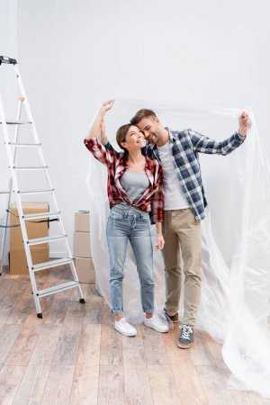 Photo for Full length of happy young couple hugging while covering with polyethylene near ladder at home - Royalty Free Image