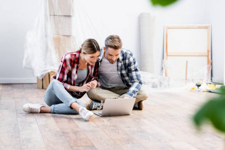 happy young couple looking at laptop while sitting on floor on blurred foreground at home