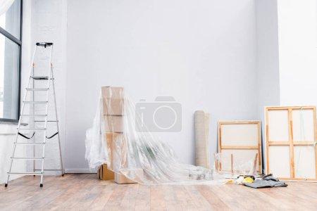 Photo pour Intérieur de la pièce avec échelle, boîtes en carton recouvertes de polyéthylène, photos et équipements pour la réparation - image libre de droit