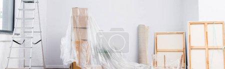 Innenraum mit Leiter, Bildern, Teppichrolle und mit Polyethylen bespannten Kartons, Banner