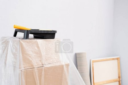 Photo pour Rouleau de peinture avec plateau sur des boîtes recouvertes de polyéthylène sur fond flou à l'intérieur - image libre de droit