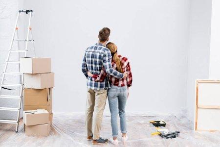 Foto de Vista trasera de la joven pareja abrazándose cerca de la escalera, cajas de cartón y rodillos de pintura en casa - Imagen libre de derechos