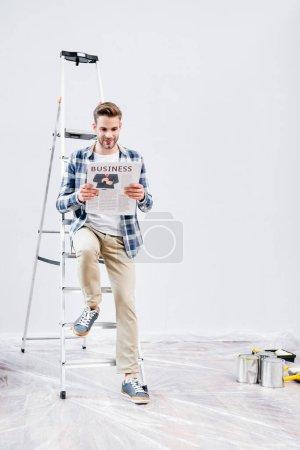 longitud completa de joven sonriente leyendo el periódico con letras de negocios mientras está sentado en la escalera cerca de latas de pintura en casa