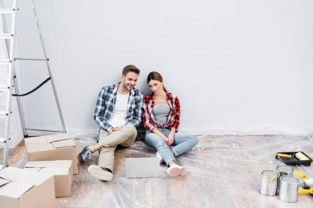 Photo for Full length of happy young couple looking at laptop while sitting on floor near cardboard boxes, tins of paint and ladder at home - Royalty Free Image