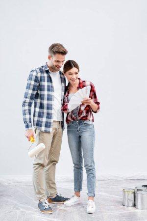 longitud completa de feliz pareja joven mirando la paleta de colores en casa