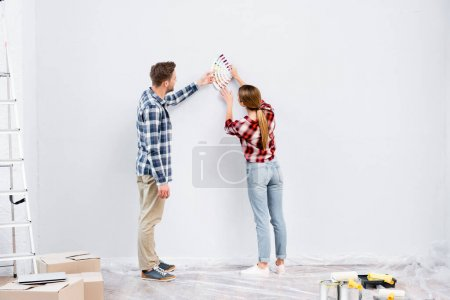 full length of young couple with palette selecting color of wall during repair at home