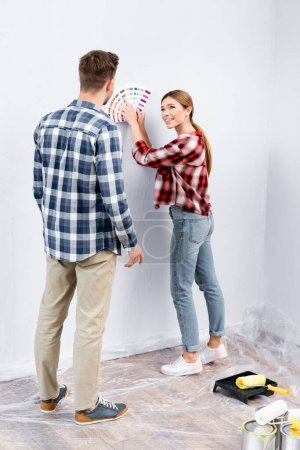 Photo for Full length of smiling young woman looking at man while pointing with finger at color palette at home - Royalty Free Image