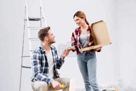 Photo for Happy young man taking piece of pizza from woman near ladder at home - Royalty Free Image