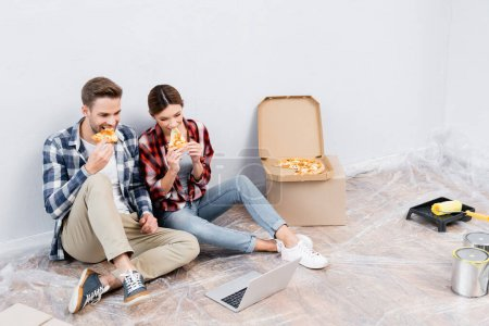 Photo for Full length of young couple eating pizza while sitting near laptop on floor at home - Royalty Free Image