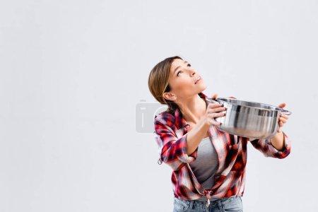 Photo pour Jeune femme levant les yeux tout en tenant la casserole sous le plafond fuyant - image libre de droit