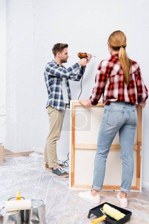 Photo pour Pleine longueur de jeune femme tenant cadre près du mur de forage de l'homme à la maison - image libre de droit