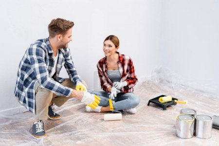 larga duración de feliz pareja joven en guantes mirándose mientras están sentados en el suelo en casa