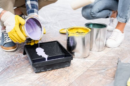 cropped view of young man in gloves pouring paint in roller tray on floor indoors