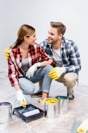 in voller Länge lächelndes junges Paar, das sich anschaut, während es zu Hause in der Hocke neben Farbdosen, Rollen und Tablett hockt
