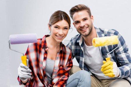 heureux jeune couple regardant caméra tout en tenant rouleaux de peinture