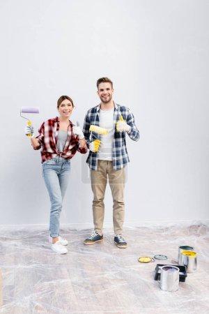 pleine longueur de jeune couple heureux avec des rouleaux de peinture regardant la caméra tout en montrant les pouces à la maison