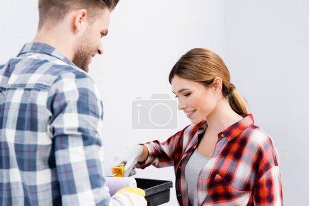 glückliche junge Frau legt Farbwalze in Tablett neben verschwommenem Mann auf Vordergrund drinnen