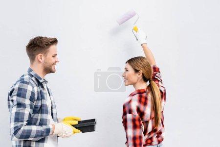 jeune femme souriante avec rouleau de peinture regardant l'homme tenant plateau isolé sur gris