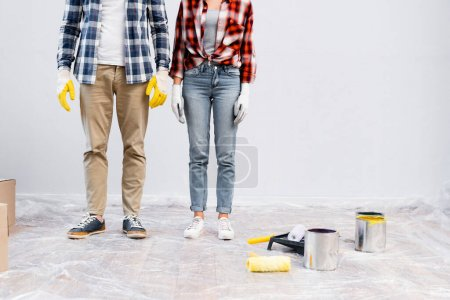 Photo for Cropped view of young couple in gloves standing near tins of paint, rollers and tray on floor covered with polyethylene - Royalty Free Image