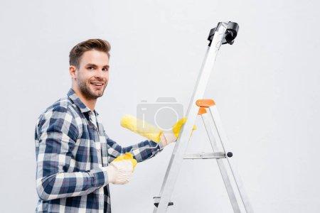 feliz joven mirando a la cámara mientras sostiene el rodillo de pintura en la escalera aislada en blanco