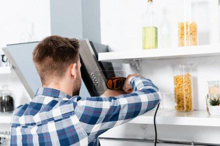 Photo pour Vue arrière du jeune homme avec perceuse réparation ventilateur extracteur sur fond flou dans la cuisine - image libre de droit