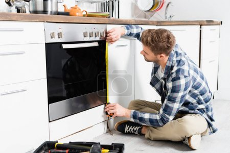 Photo for Full length of young man with tape measuring oven while sitting near toolbox on floor - Royalty Free Image
