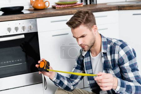 serious young man looking at tape measure near oven in kitchen