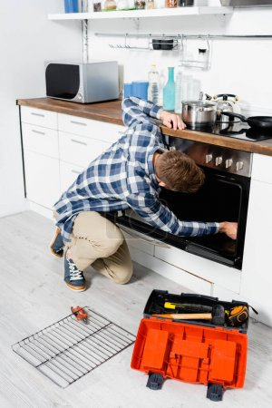 Photo for Full length of young man repairing oven while sitting on floor near grid and toolbox in kitchen - Royalty Free Image