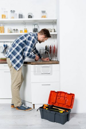 full length of young man with pliers bending over sink near open toolbox in kitchen