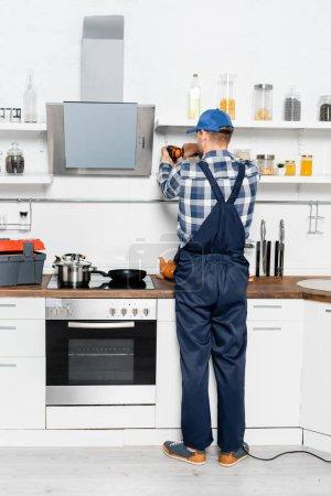 Photo pour Vue arrière de bricoleur avec perceuse réparation étagères dans la cuisine - image libre de droit
