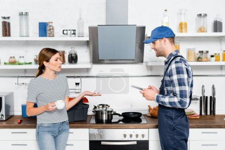young woman with cup of coffee talking to handyman with tablet in kitchen