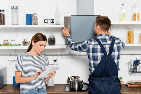 young woman using tablet near handyman repairing extractor fan in kitchen