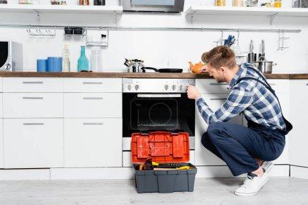 Photo pour Longueur totale du jeune réparateur tournant bouton du four tout en étant assis près de la boîte à outils dans la cuisine - image libre de droit
