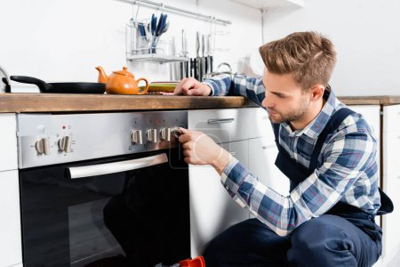 young handyman turning oven button in kitchen