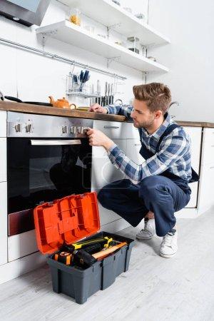 Photo pour Pleine longueur de jeune bricoleur vérifier le bouton du four tout en étant assis près de la boîte à outils dans la cuisine - image libre de droit