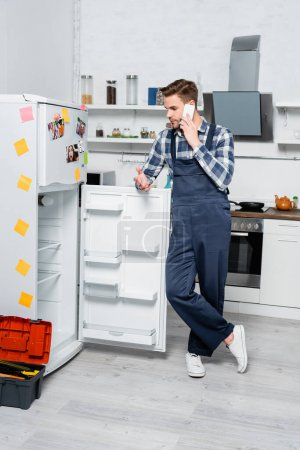 full length of young repairman talking on smartphone while leaning on fridge near toolbox in kitchen