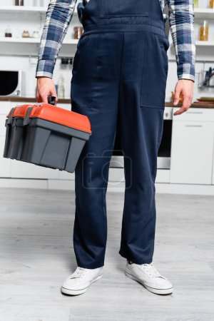 Photo for Cropped view of young handyman holding toolbox with blurred kitchen on background - Royalty Free Image