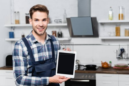 front view of happy handyman looking at camera while showing tablet with blurred kitchen on background