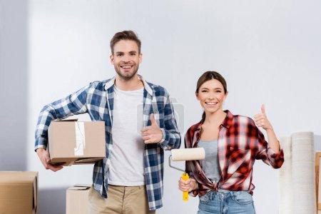 Photo pour Vue de face du jeune couple heureux avec boîte et rouleau de peinture montrant pouces vers le haut tout en regardant la caméra à l'intérieur - image libre de droit