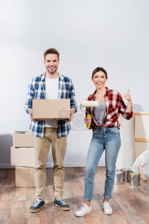 Photo for Full length of happy young woman with paint roller showing thumb up near man with cardboard box at home - Royalty Free Image