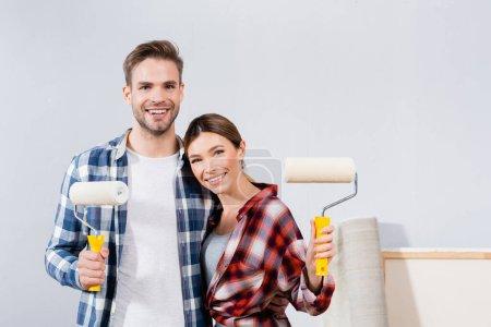 vista frontal de feliz pareja joven con rodillos de pintura mirando a la cámara mientras se abraza en casa