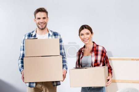 Photo for Front view of cheerful young couple looking at camera while holding cardboard boxes at home - Royalty Free Image