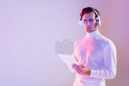 Photo for Cyborg in white clothes and headphones holding digital tablet on purple background - Royalty Free Image