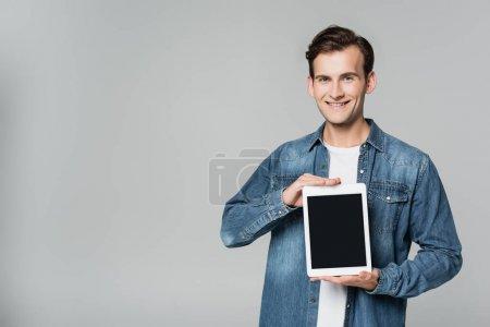 Photo pour Homme positif montrant tablette numérique avec écran blanc isolé sur gris - image libre de droit