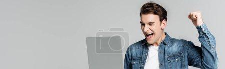 Photo pour Homme positif montrant geste oui tout en regardant ordinateur portable isolé sur gris, bannière - image libre de droit