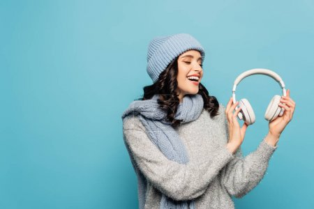 Photo for Happy brunette woman in winter outfit looking at headphones isolated on blue - Royalty Free Image