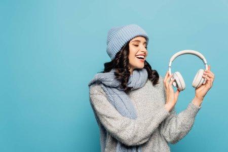 Photo pour Heureuse femme brune en tenue d'hiver regardant des écouteurs isolés sur bleu - image libre de droit