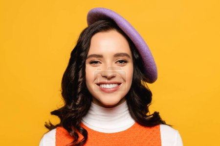 Photo for Portrait of smiling brunette woman in beret looking at camera isolated on yellow - Royalty Free Image