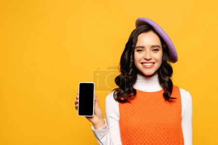 Photo for Happy brunette woman in beret looking at camera while showing smartphone isolated on yellow - Royalty Free Image
