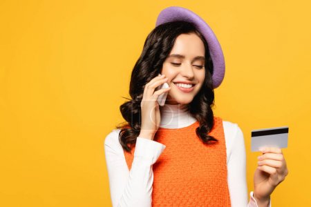 Photo for Smiling brunette woman in beret talking on cellphone while looking at credit card isolated on yellow - Royalty Free Image